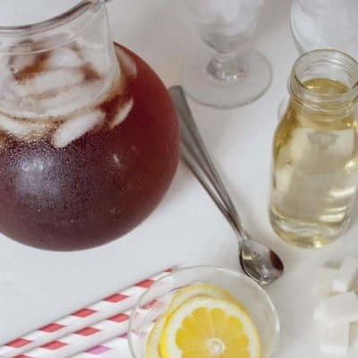 Pitcher of iced tea, bottle of simple syrup, lemon slices, and straws.