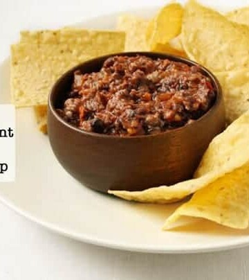 2 Ingredient Black Bean Dip in a wood bowl on a platter surrounded by tortilla chips.