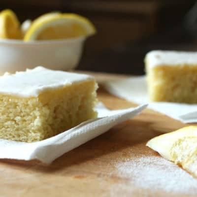 Gluten-free lemon cake squares on wood board.