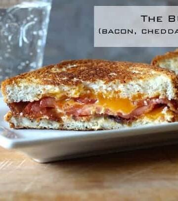 Bacon, Cheddar, Tomato Sandwich on white platter.