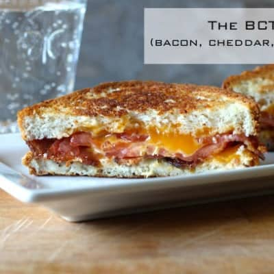 Bacon, Cheddar, Tomato Sandwich on white platter.