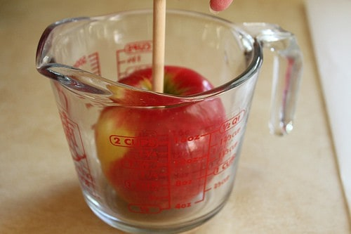 Apple in empty glass measuring cup.