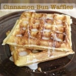 Gluten-Free cinnamon bun waffles on plate with glaze.