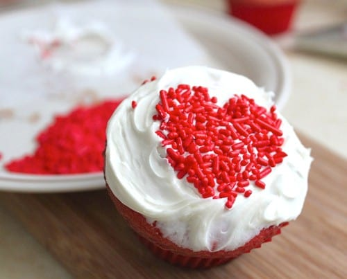 Cupcake with white frosting and red sprinkle hearts.
