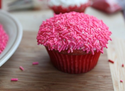 Gluten-free cupcake topped with frosting and covered with pink sprinkles.
