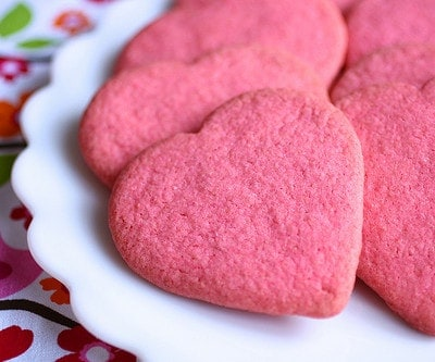Pink gluten-free sugar cookie hearts on a plate.