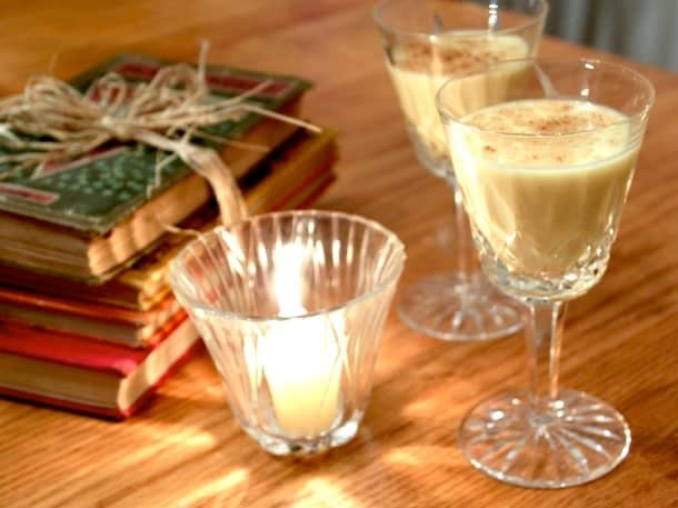 Two glasses of eggnog next to a candle and stack of old books.