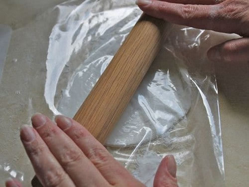 Rolling gluten-free flour tortilla dough with rolling pin.