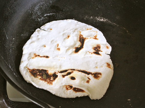 Cooked gluten-free Flour tortilla in a skillet with brown spots.