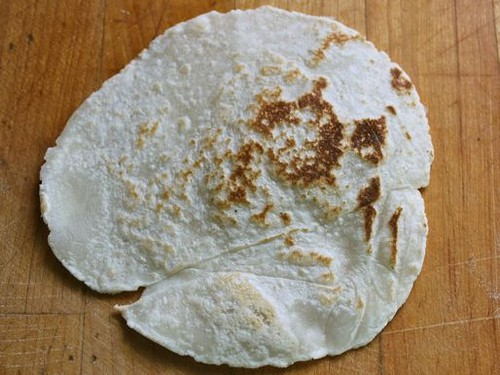 Gluten-free flour tortilla with brown spots.