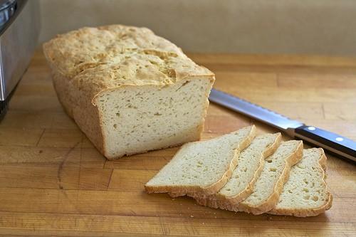 Gluten-free loaf of bread sliced on a cutting board.