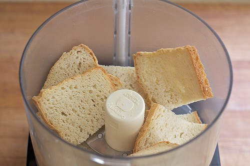 Gluten-free bread slices in the bowl of a food processor.