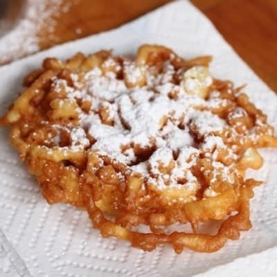 Gluten-free funnel cake dusted with powdered sugar on paper towel.