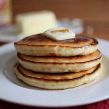 Stack of gluten-free pancakes with pat of butter and drizzle of syrup.