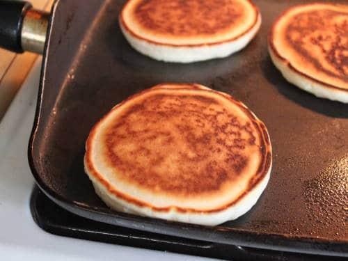Gluten-free pancakes on skillet.