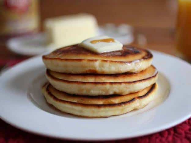 Fluffy Gluten Free Pancakes with a pat of butter and drizzle of syrup.