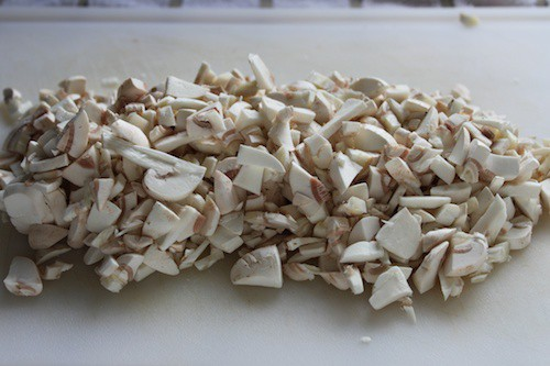 Chopped mushrooms on a white cutting board.