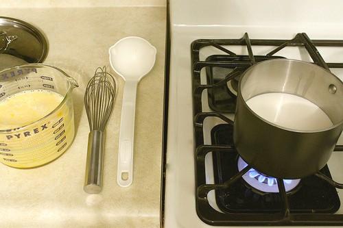 Ingredients for homemade eggnog. Milk in saucepan.