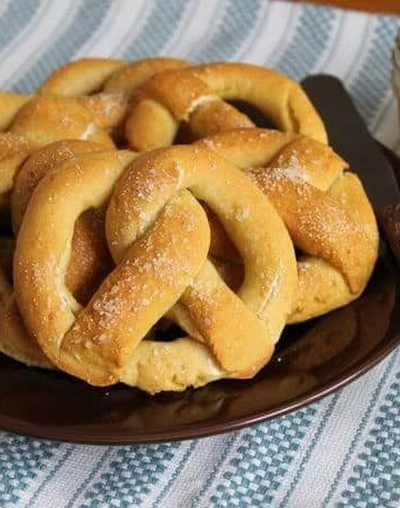 Gluten-free pretzels on a plate with a jar of mustard sitting to the right.