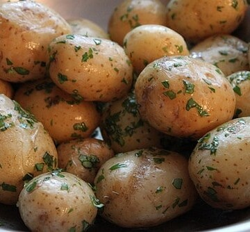 Steamed potatoes coated in butter and herbs.