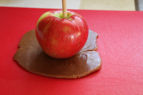 Red apple sits on top of rolled out caramel.