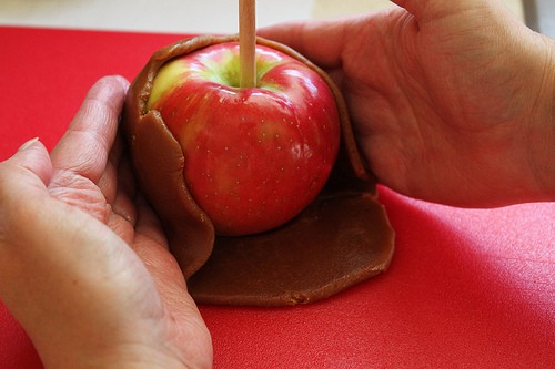 Wrapping a red apple in caramel.