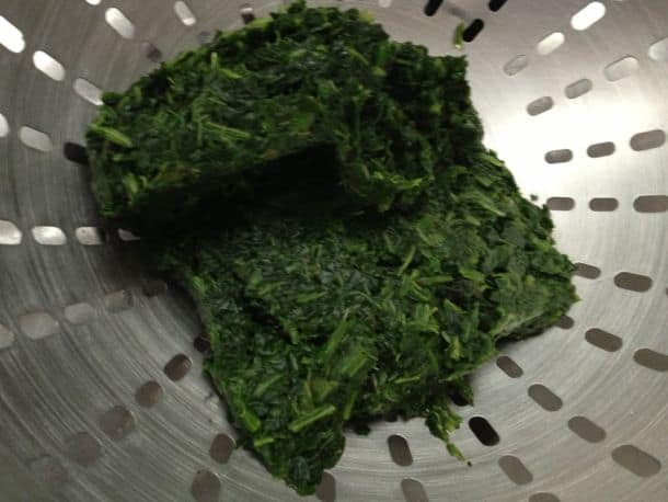 Draining liquid from chopped spinach.