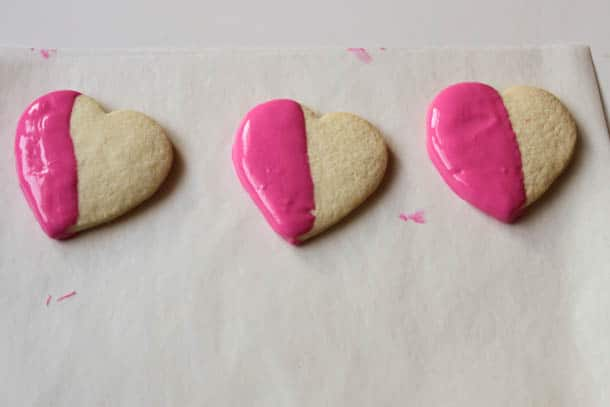 Three gluten-free heart shaped cookies half dipped in pink chocolate.