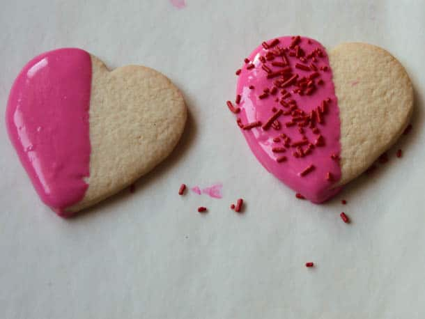 Two gluten-free heart shaped cookies half dipped in pink chocolate.