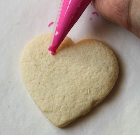 Gluten-free sugar cookie hearts being frosted with pink frosting.