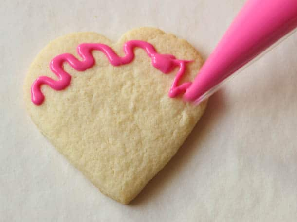 Gluten-free sugar cookie hearts frosted with pink squiggle frosting.