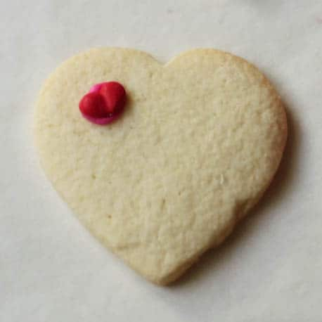 Gluten-free sugar cookie hearts frosted with small icing heart.