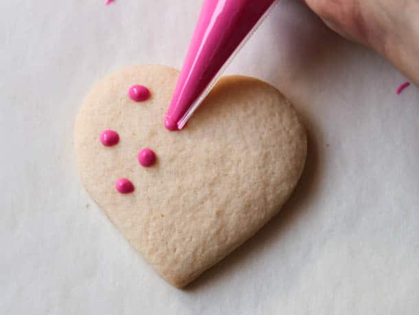 Piping pink chocolate polka dots on gluten-free heart cookie.