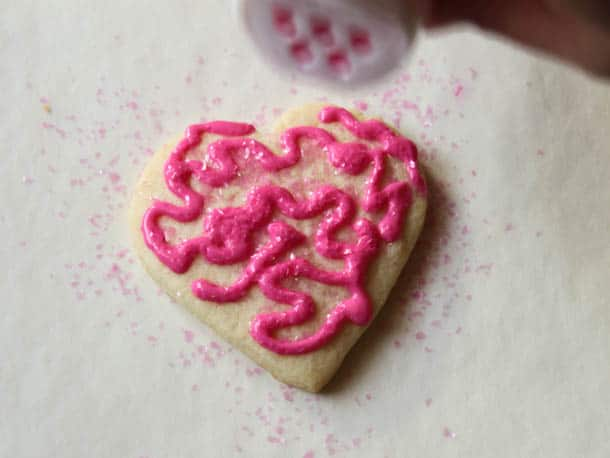 Sprinkling edible glitter on a gluten-free sugar cookie.