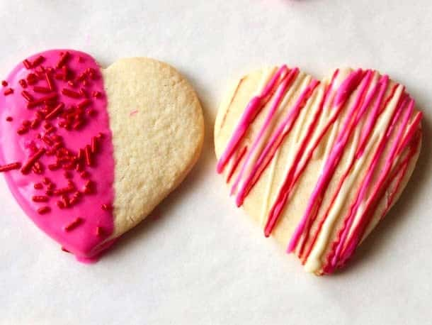 Cookie dipped in pink chocolate with sprinkles. Cookie drizzled with red, pink, and white chocolate.