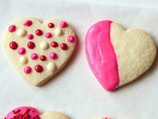 Polka dot decorated gluten-free sugar cookie. Second cookie is half dipped in pink chocolate.