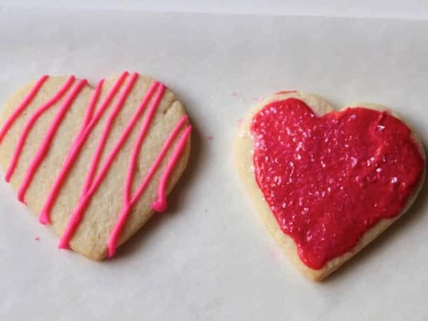 Gluten-free sugar cookie hearts frosted with red frosting.