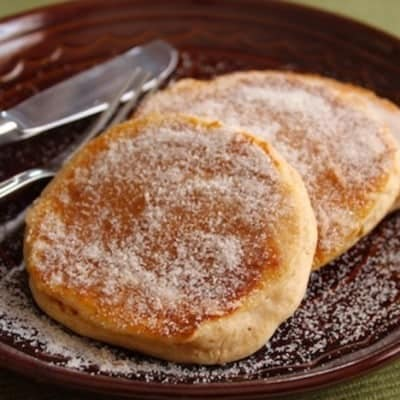 Apple Cider Doughnut Pancakes on a plate coated with granulated sugar.