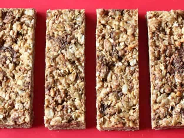 Chewy granola bars on red cutting board.