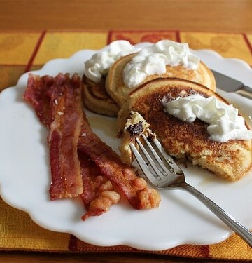 Gluten-free chocolate chip pancakes topped with whipped cream on a plate with bacon.