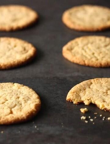 Momofuku Milk Bar's Corn Cookies on a baking sheet. One cookie has a bite taken out of it.