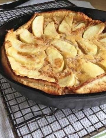 Gluten-Free Dutch Apple Pancake in a skillet set on a cooling rack.