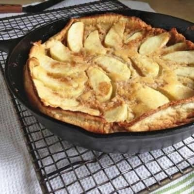 Gluten-Free Dutch Apple Pancake in a skillet set on a cooling rack.