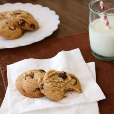 Gluten-free brown butter chocolate chip cookies on a napkin. A glass of milk and a platter of cookies is in the background.