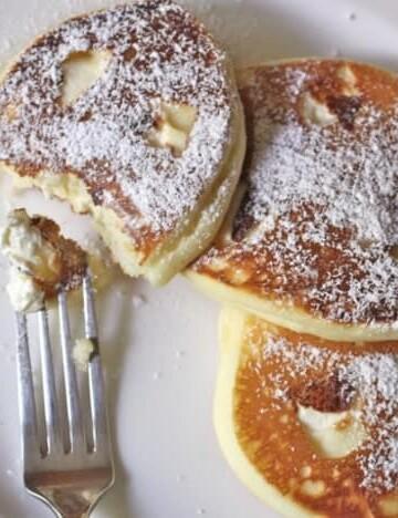 Gluten-Free Cheesecake Pancakes on a white plate.