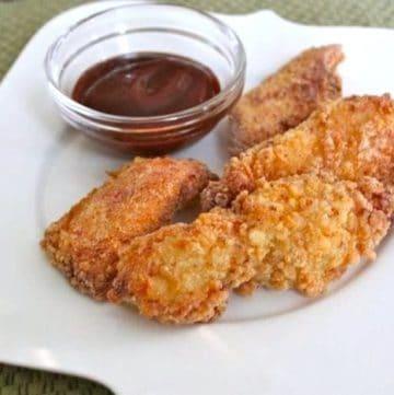 Gluten-Free Crispy Chicken Fingers on a white plate.
