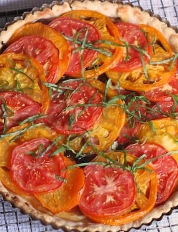 Gluten-Free Tomato Tart on a wire rack. The tart is topped with shredded basil.