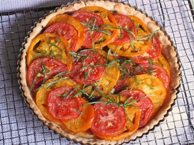 Gluten-Free Tomato Tart on a cooling rack. The tart is topped with shredded basil.