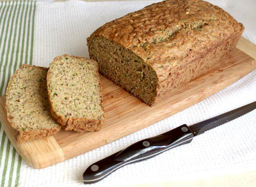 Gluten-Free Zucchini Bread sliced on a wood cutting board.