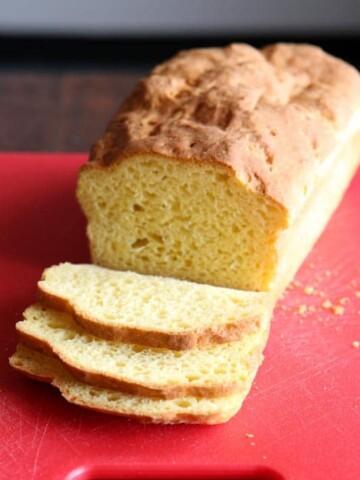 Loaf of Baked Gluten-Free Sandwich Bread on Red Cutting Board.